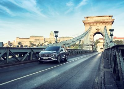 The new Hyundai Santa Fe 7 seat SUV in grey driving over a city bridge.