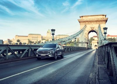 The new Hyundai Santa Fe Hybrid 7 seat SUV in grey driving over a bridge.
