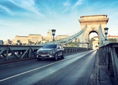 El nuevo Hyundai SANTA FE Híbrido de 7 plazas conduciendo en una carretera.