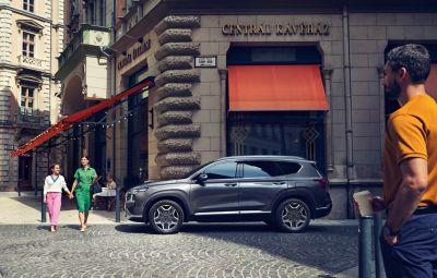 Nowy 7-miejscowy SUV Hyundai Santa Fe Hybrid w kolorze szarym zaparkowany na miejskiej ulicy.