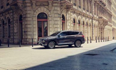 Nowy 7-miejscowy SUV Hyundai SANTA FE Plug-in Hybrid zaparkowany na miejskiej ulicy.