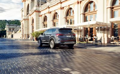 The new Hyundai Santa Fe Hybrid 7 seat SUV from the rear driving through a city.
