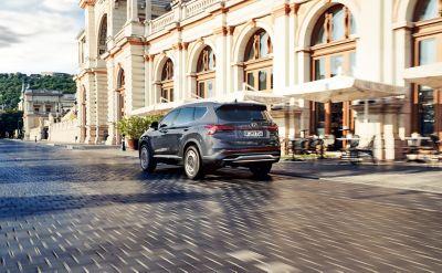 The new Hyundai Santa Fe Hybrid 7 seat SUV in grey driving down a city street.