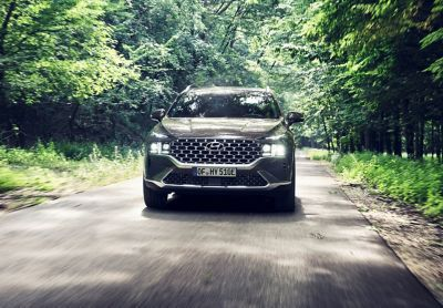 The newHyundai Santa Fe Plug-in Hybrid 7 seat SUV driving on a forest road.
