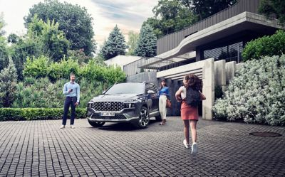 The new Hyundai Santa Fe 7 seat SUV in grey parked in front of a luxurious family house.
