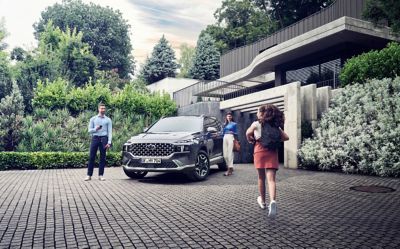 The new Hyundai Santa Fe Hybrid 7 seat SUV in grey parked in front of a luxurious family house.