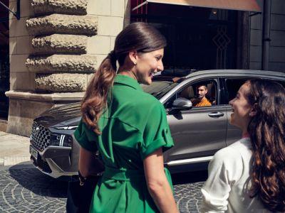 Kobieta z córką uśmiechają się do siebie, mężczyzna siedzi w samochodzie.