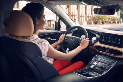 Interior view of the new Hyundai Santa Fe 7 seat SUV showing a woman driving down a city street.