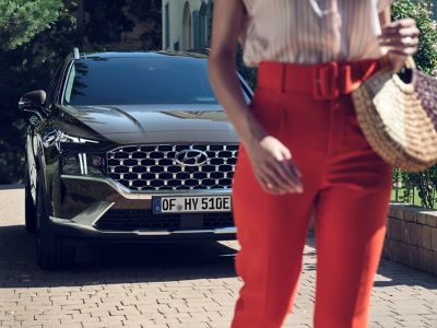 A woman standing in front of the new Hyundai Santa Fe Plug-in Hybrid 7 seat SUV parked.