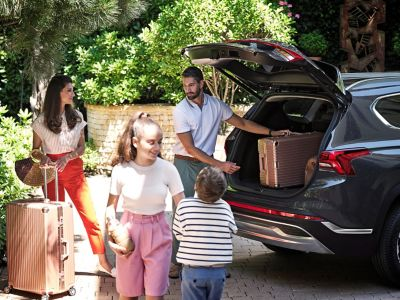 A family loading the trunk of the new Hyundai Santa Fe Hybrid 7 seat SUV.