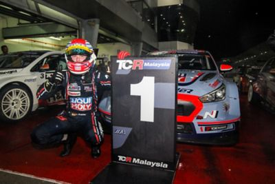 A driver posing with the sign of the TCR Malaysia race.