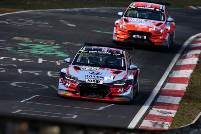 A picture of Hyundai Motorsport customer racing i30 N TCR in action on a racetrack.