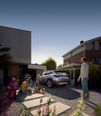 Il Nuovo SUV compatto Hyundai TUCSON Plug-in Hybrid parcheggiato di fronte a una casa con una famiglia.
