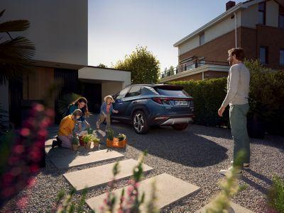 Samochód Hyundai Tucson zaparkowany przed domem, obok stoją dzieci i mężczyzna.