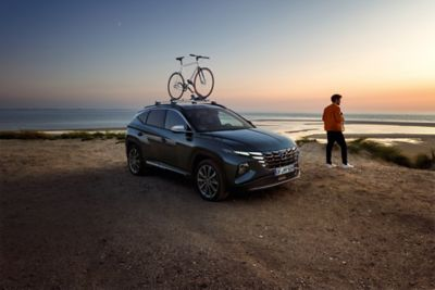 The Hyundai TUCSON with genuine accessories in the sunset at a beach.