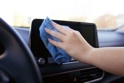 Dame vasker skjerm i bil med klut. Foto.