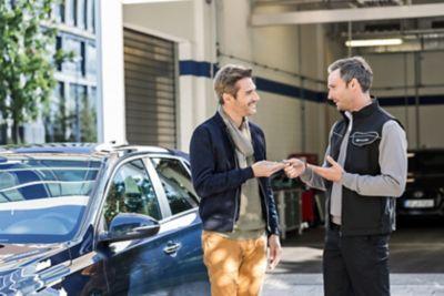 Ekspert serwisowy ASO Hyundai przekazuje mężczyźnie klucze do samochodu zastępczego.