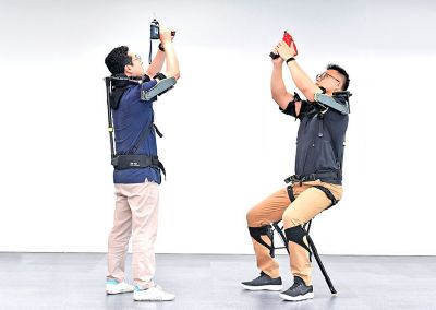 Two men trying out Hyundai's VEX exoskeleton vest in working conditions