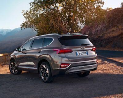 Immagine di Hyundai Santa Fe parcheggiata davanti a un panorama montuoso.