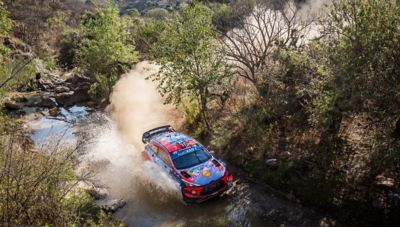 The Hyundai i20 Coupe WRC driving through a body of water.