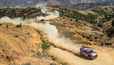 The Hyundai i20 Coupe WRC driving through the desert and being followed by a helicopter.