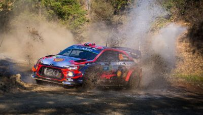 The Hyundai i20 Coupe WRC driving through a puddle.