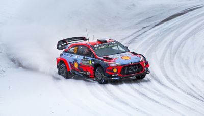 The Hyundai i20 Coupe WRC driving on a snow-covered road.