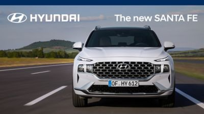 The new Hyundai Santa Fe Hybrid 7 seat SUV in white driving down a highway.