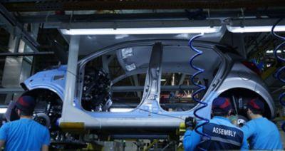 Tre personer arbeider på en bil på Hyundai-fabrikken. Foto