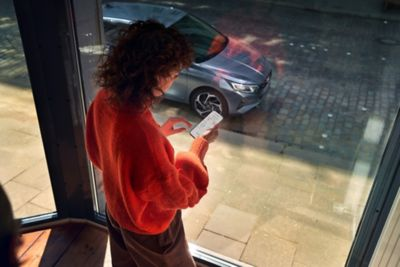 A woman looking at the Hyundai Bluelink App on her smartphone, her Hyundai i20 is parked outside.