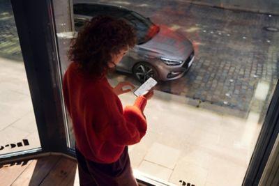 Een vrouw in rode sweater maakt verbinding met de nieuwe i30 Hatchback via haar smartphone.