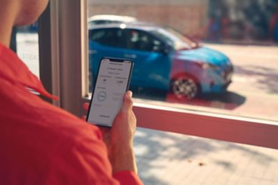 A woman looking at the Hyundai Bluelink App on her smartphone, her car is parked outside.
