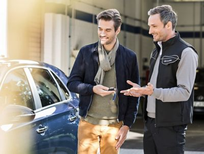 A Hyundai dealer showing a customer a brandnew Hyundai at the dealership.