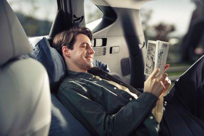 Mężczyzna czytający książkę w środku samochodu Hyundai.