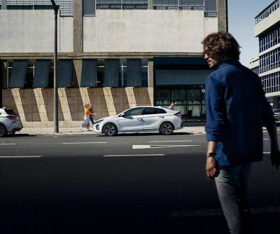 Mężczyzna przechodzi przez ulicę, kieruje się do swojego Hyundaia IONIQ.