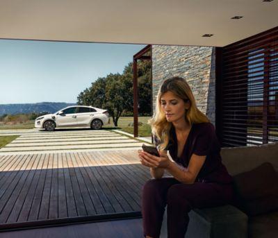 Kobieta sprawdza ofertę Hyundai Promise na telefonie komórkowym.