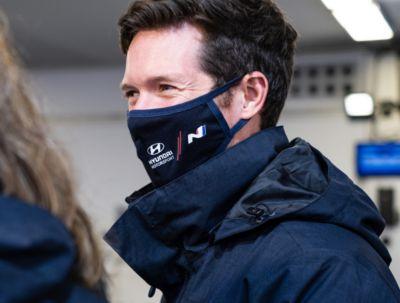 Hyundai Motorsport co-driverMartijn Wydaeghe smiling at crew members with mask.
