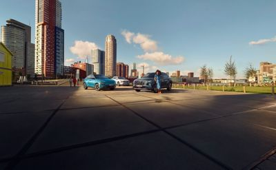 Hyundai's family of electrified cars parked in front of a cityscape.
