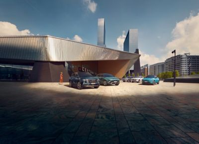 Immagine di 5 SUV elettrificati Hyundai parcheggiati di fronte ad un teatro futuristico