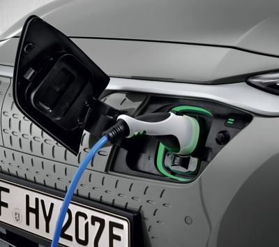 Charging socket of the Hyundai KONA Electric with a plugged in charging cable