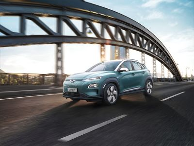 The Hyundai KONA Electric driving on a bridge