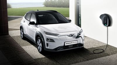 Hyundai KONA electric plugged into a wallbox in a garage
