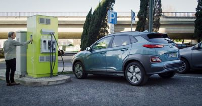 Hyundai KONA Electric standing at a public fast-charging station