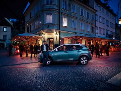Man leaning against a Hyundai KONA Electric in the busy street by night