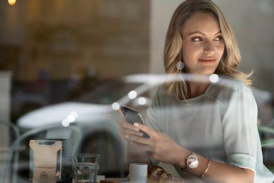 Femme souriant, avec le reflet de Hyundai IONIQ dans la fenêtre.