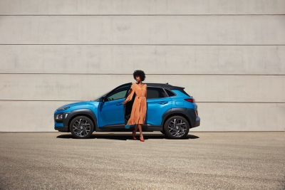 Lady dressed in orange getting off a Hyundai KONA Electric