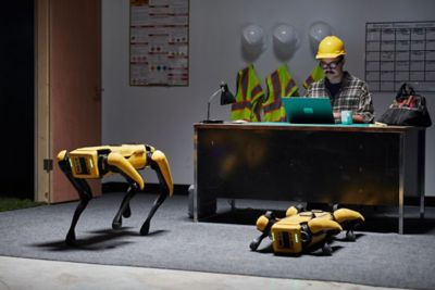 Worker sitting at a desk with Boston Dynamics Spot robots waiting for instructions.