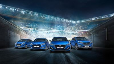 Four Hyundai models standing before a crowded stadium.