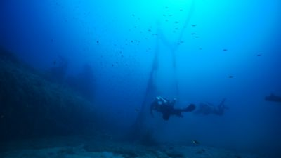 Two divers from Ghost Divers recovering marine debris underwater.