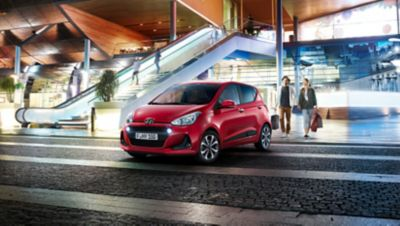 The Hyundai i10, shown from the front, standing before a futuristic shopping centre.